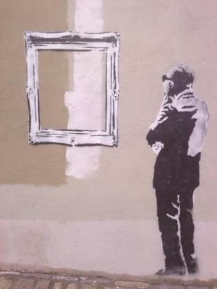 stencil graffiti of a man contemplating an empty (?) picture frame